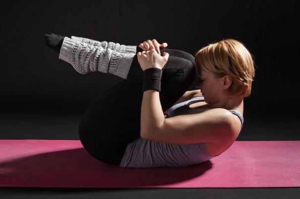 54898944 - young woman practicing yoga, pawanmuktasana / wind relieving pose